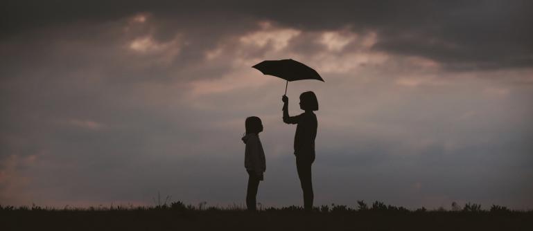 dark clouds with people standing under an umbrella